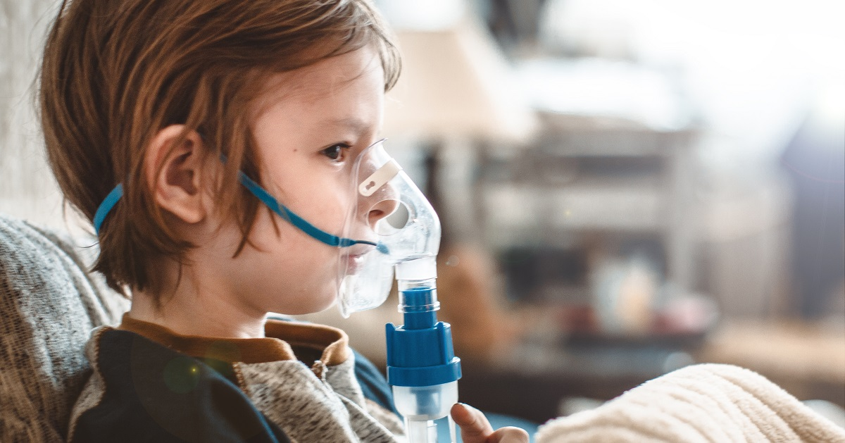 child using inhaler mask for asthma