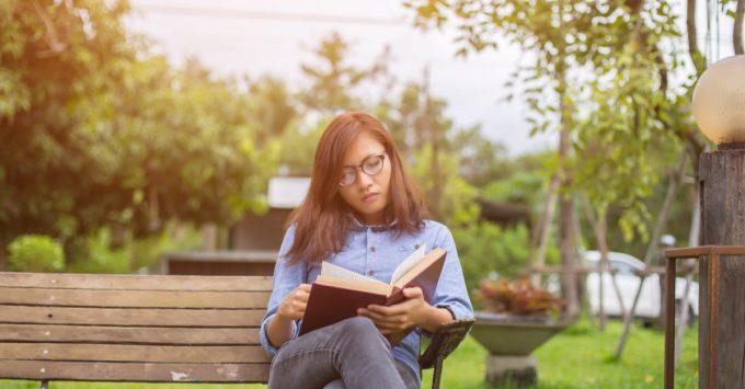 Girl Reading Book on Park Bench