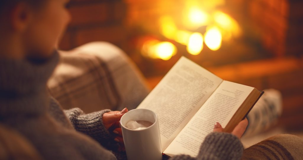 holiday self-care tips - reading cozy by fire