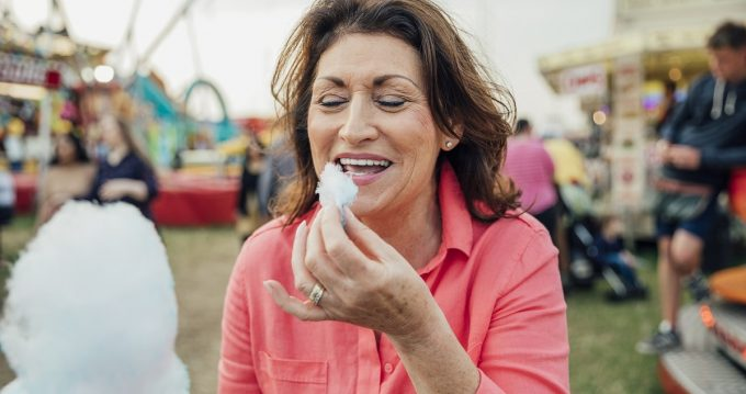 Senior woman visiting the fairground to enjoy the rides. She is enjoying eating cotton candy