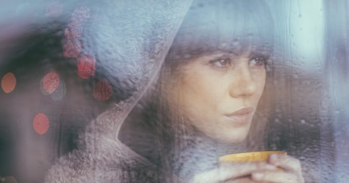 young woman looking through the window on a rainy day