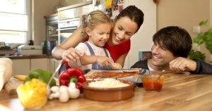 Happy family in kitchen preparing pizza