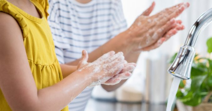 Mom shows daughter proper way to wash hands