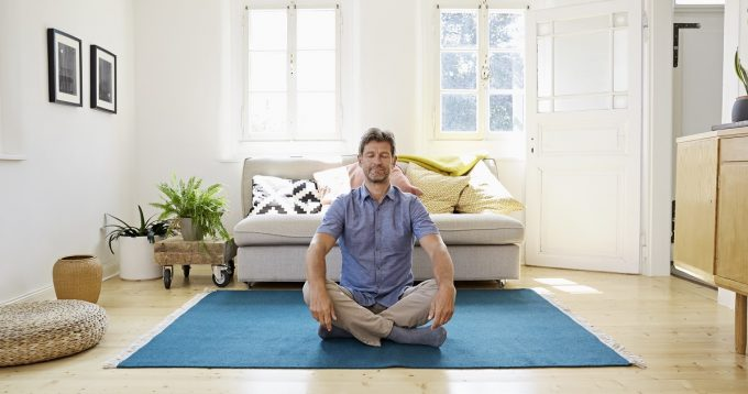 Man meditating at home