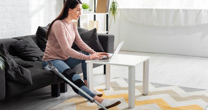 Woman with broken leg looking at computer