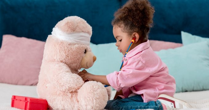 Girl examining teddy bear