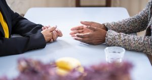 Hands across table
