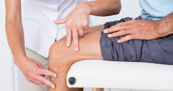 Doctor examining patients knee