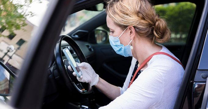 Woman in mask getting out of car