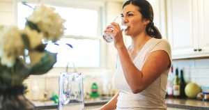 Woman drinking water in kitchen