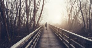 Woman walking on foggy bridge