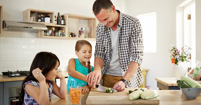 Father and daughters in kitchen