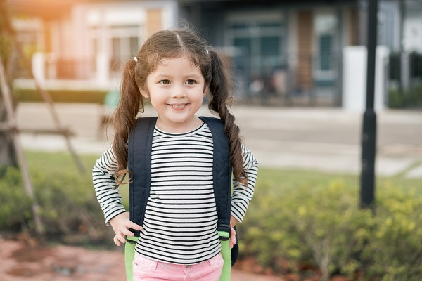Happy Schoolgirl Carrying Backpack While Standing On Footpath